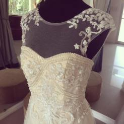 Lace bodice embellished with beaded floral detail and topped off by illusion sleeves.