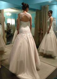 Drop waist wedding dress made of tulle and lace. The lace bodice is encrusted with bead work for more glamour. The features an illusion cut out.