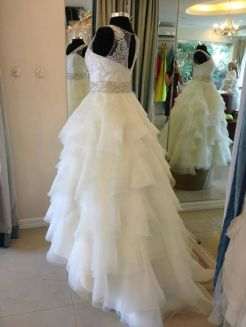 A flounced ruffle layered organza skirt is the star feature of this wedding ball gown.