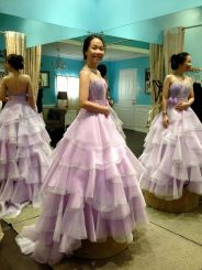 A purple ball gown with a bejeweled asymmetrical strap and a flounced organza skirt.